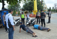 Dua karyawan PLN saat disanksi petugas karena terjaring Operasi Yustisi di Tugu Kuning, Kampung Tri Tunggal Jaya, Kecamatan Banjar Agung