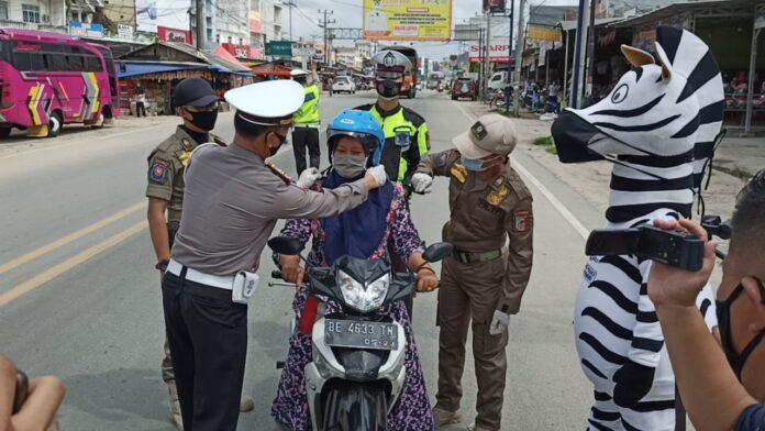 Pengendara yang mendapatkan helm gratis dari Satlantas Polres Tulang Bawang saat mengelar Gebyar Simpatik pada Operasi Zebra Krakatau-2020 di Pasar Unit 2