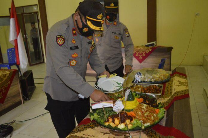 Wakapolres Tulang Bawang Kompol Nelson Manik, SH memotong nasi tumpeng pada peringatan HUT Satpam Ke-40 di GSG Wira Satya Mapolres Tulang Bawang